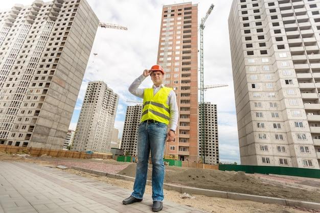 建築現場に立っているヘルメットと安全ベストの青年実業家