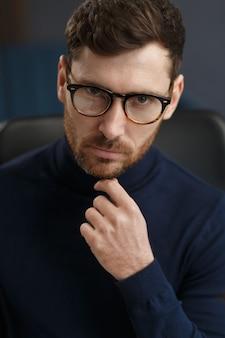 Молодой бизнесмен в офисе бизнес-портрет красивого бородатого мужчины в очках, сидящего на ...