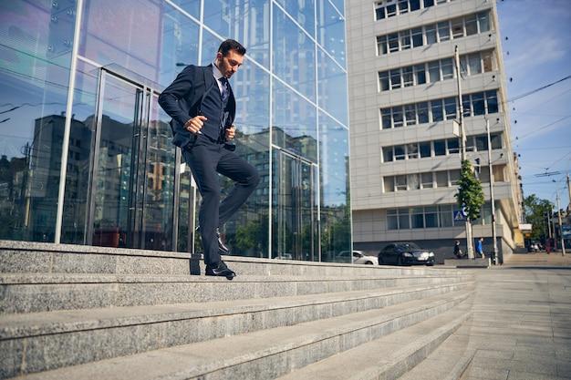 ガラス張りの美しいビジネスセンターを出て急ぐ公務衣の青年実業家 Premium写真