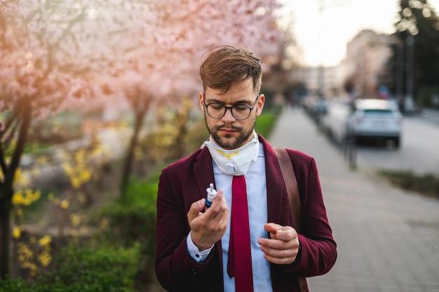 Молодой бизнесмен в парке, держа капли в нос. аллергия, грипп, вирусная концепция.