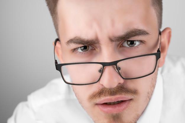 Молодой бизнесмен в рубашке и очках, шокирован на сером студийном фоне