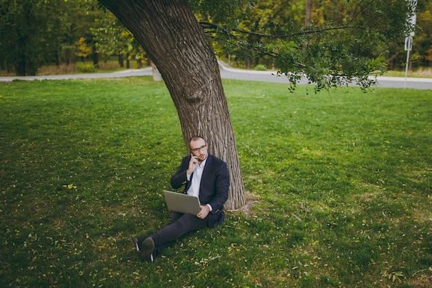 シャツ、スーツ、眼鏡の青年実業家。男は草地に座って、携帯電話で話し、自然の屋外の緑の芝生の都市公園でラップトップpcコンピューターで作業します。モバイルオフィス、ビジネスコンセプト。