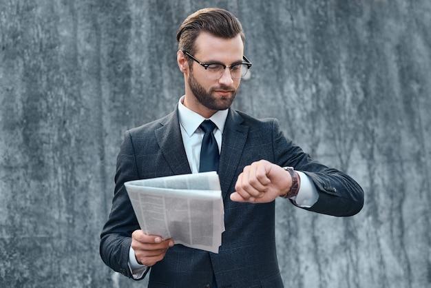 양복과 안경을 쓴 젊은 사업가가 시계를 보고 비즈니스 신문을 읽는다