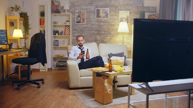 Молодой бизнесмен в костюме и галстуке расслабляющий, пьющий пиво и просматривающий телефон после тяжелого рабочего дня,
