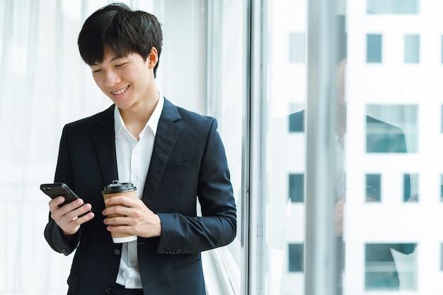 커피를 마시고 창으로 전화를 사용하는 소송에서 젊은 사업가