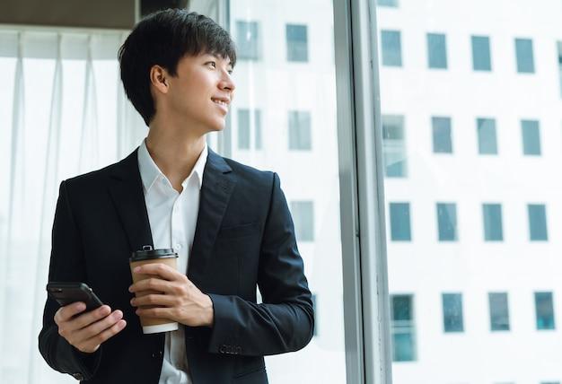 コーヒーを飲み、窓際の電話を使用してスーツを着た青年実業家