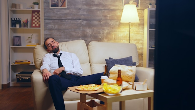 Молодой бизнесмен в костюме засыпает на диване, все еще одетый в костюм