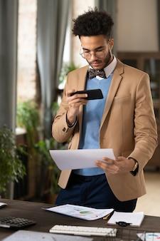 Молодой бизнесмен в костюме, фотографируя документы на мобильный телефон для отправки
