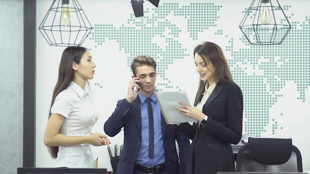 電話で話しているスーツの青年実業家とオフィスでの仕事について話し合っている2人の若い女性従業員