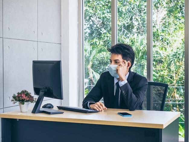 コンピューターで作業し、巨大なガラス窓の近くのオフィスの机の上のスマートフォンで疲れた顔で緊張して考えている保護フェイスマスクを身に着けているスーツの青年実業家。
