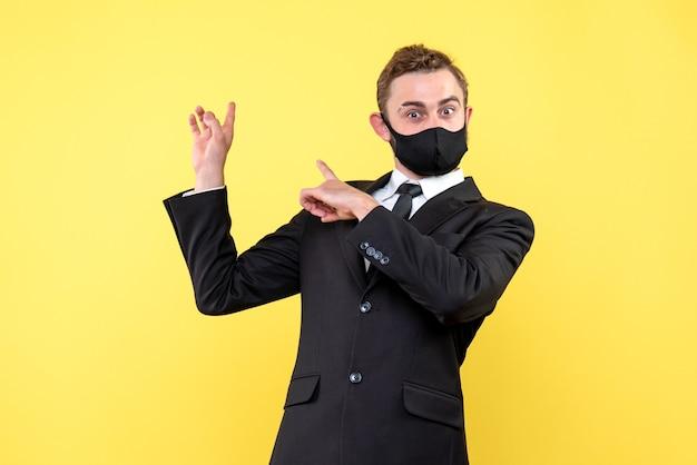 Молодой бизнесмен в костюме с удивленным выражением лица, указывая на правую сторону