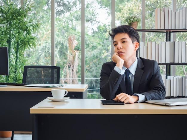 Молодой бизнесмен в костюме с проблемами, усталым, напряженным и грустным скучным сидением с рассеянным на своем столе в офисе.