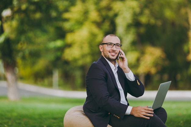 흰 셔츠, 고전적인 양복, 안경을 쓴 젊은 사업가. 남자는 부드러운 푸프에 앉아 전화 통화를 하고 도시 공원에서 야외 자연의 푸른 잔디밭에 있는 노트북 컴퓨터에서 일합니다. 모바일 오피스, 비즈니스 개념입니다.