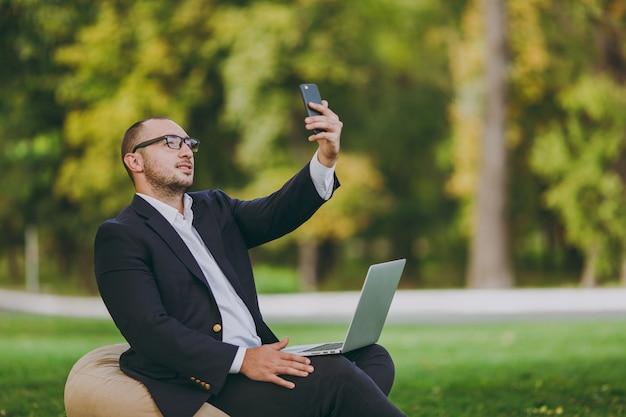 白いシャツ、古典的なスーツ、眼鏡の青年実業家。男はラップトップpcコンピューターで柔らかいプーフに座って、屋外の緑の芝生の都市公園で携帯電話で自分撮りをしています。モバイルオフィスのビジネスコンセプト。