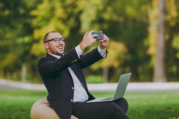白いシャツ、古典的なスーツ、眼鏡の青年実業家。男はラップトップpcコンピューターで柔らかいプーフに座って、屋外の緑の芝生の都市公園で携帯電話で自分撮りをしています。モバイルオフィスのビジネスコンセプト。 無料写真