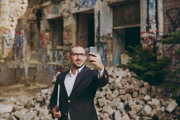 흰 셔츠, 고전적인 양복, 안경을 쓴 젊은 사업가. 노트북 컴퓨터와 함께 서 있는 남자, 폐허 잔해 근처에서 휴대전화로 셀카를 찍고, 야외에서 석조 건물을 짓고 있습니다. 모바일 오피스, 비즈니스 개념입니다.