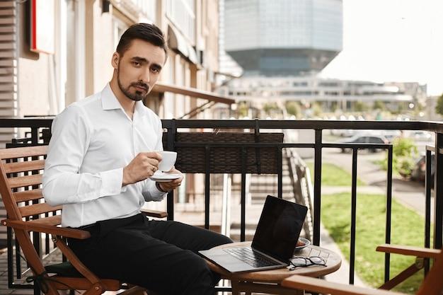 コーヒーを飲み、カフェのテーブルで彼のラップトップを使用して白いシャツを着た青年実業家