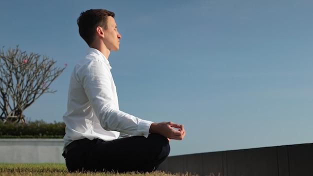 Молодой бизнесмен в белой рубашке медитирует, сидя в позе лотоса на террасе отеля на солнечном свете против вида сбоку голубого неба