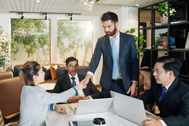 会議で自己紹介と女性起業家の手を振る青年実業家