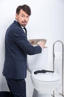 Young businessman is hiding money in the toilet tank.