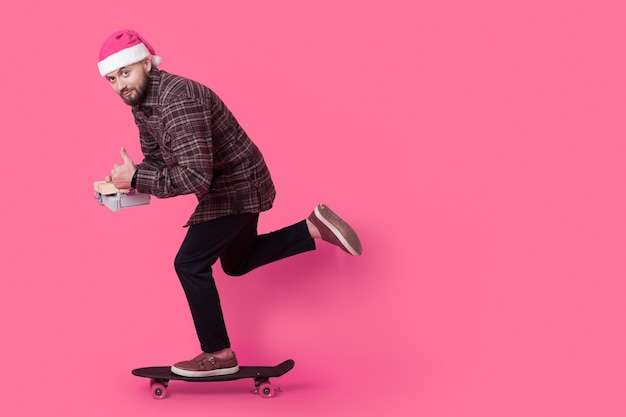 Молодой бизнесмен катается на скейтборде в шляпе санта-клауса и держит подарки на розовой стене со свободным пространством