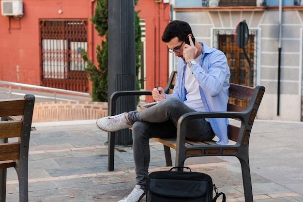 Young businessman is sitting on a bench while he is talking on the mobile and is writing in his notebook