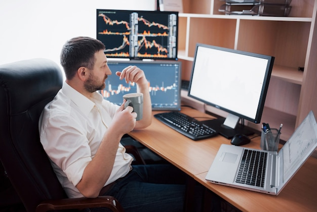 Young businessman is sitting in office at table, working on computer with many monitors,diagrams on monitor. stock broker analyzes binary options charts.hipster man drinking coffee,studying.
