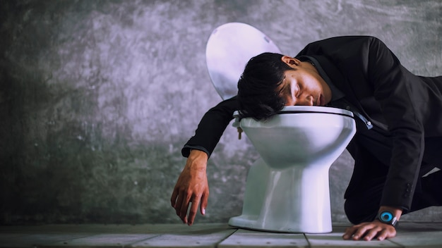 A young businessman is sleeping in the bathroom