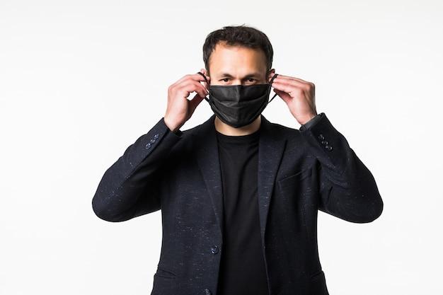 Молодой бизнесмен примеряет медицинскую маску во время пандемии коронавируса