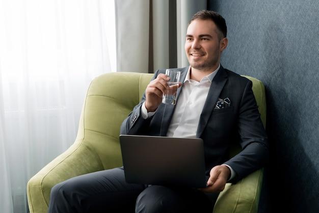 젊은 사업가 가방과 함께 호텔 방에 앉아있는 동안 노트북과 식수를 사용하고 있습니다.