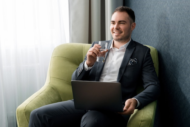Young businessman is using laptop and drinking water while sitting at the hotel room with suitcase.