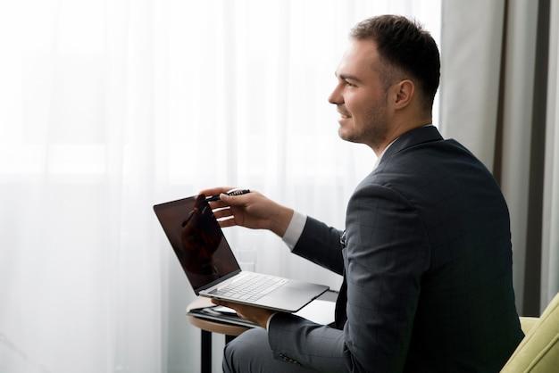 若いビジネスマンはスーツケースを持ってホテルの部屋に座っている間ラップトップを使用しています。
