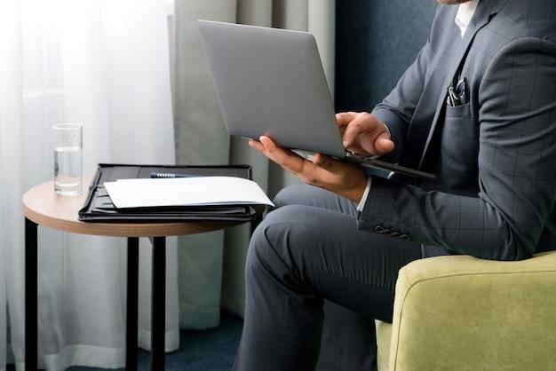 若いビジネスマンはホテルの部屋に座っている間ラップトップを使用しています