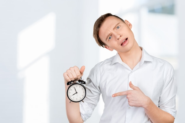 Young businessman keeping clock