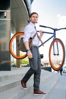 Молодой бизнесмен покидает офисное здание после работы и несет велосипед, спускаясь по лестнице в городской среде