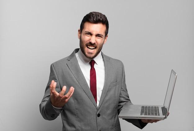 젊은 사업가 화가, 짜증이 나고 좌절 비명을 지르며 비명을 지르거나 당신에게 무엇이 문제인지 노트북을 들고