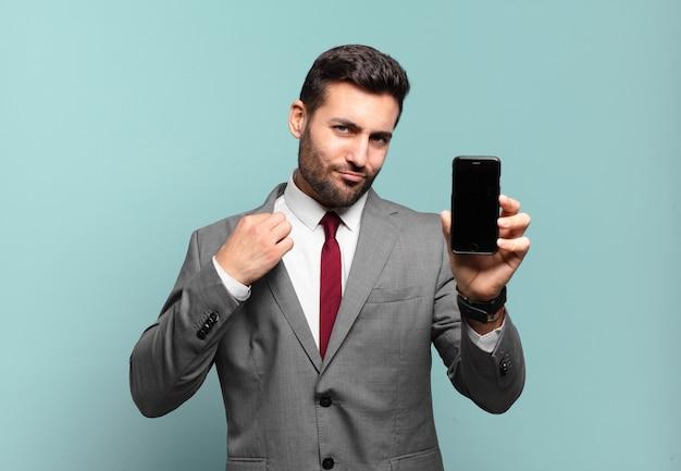 거만하고, 성공하고, 긍정적이고, 자랑스럽고, 자기를 가리키고 자신의 전화 화면을 보여주는 젊은 사업가