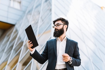 Young businessman looking at digital tablet standing in front of building