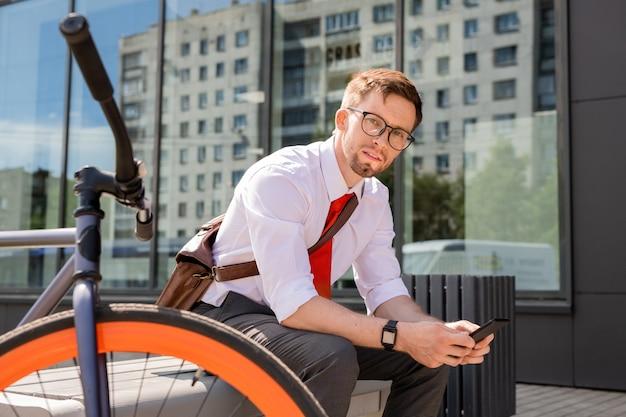 ベンチに座って、仕事の後に都市環境でスマートフォンを使用しながらあなたを見ている青年実業家
