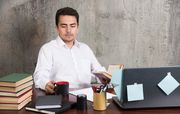 Молодой предприниматель, глядя на офисный стол.