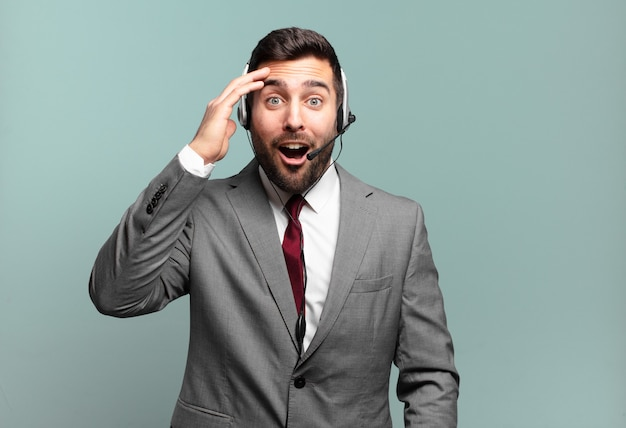 Young businessman looking happy, astonished and surprised, smiling and realizing amazing and incredible good news telemarketing concept