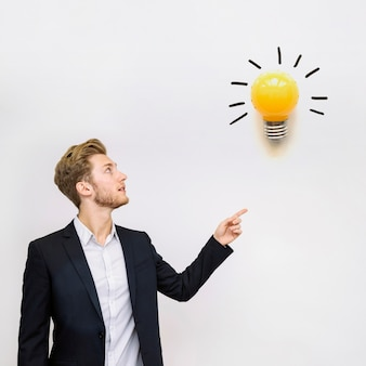 Young businessman looking at a light bulb