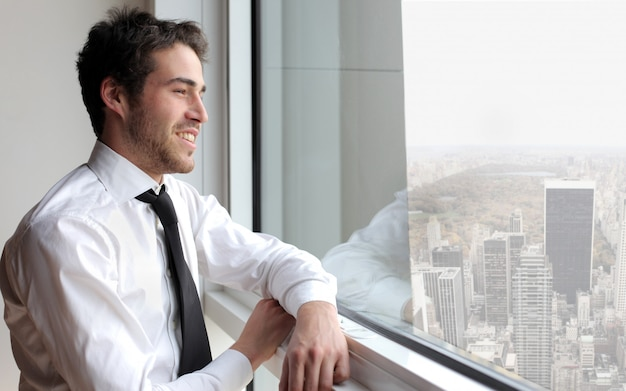 Young businessman looking out of the window