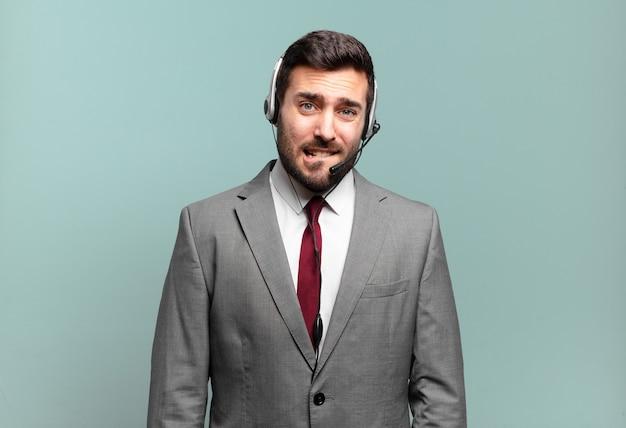 Молодой бизнесмен выглядит озадаченным и сбитым с толку, нервно закусив губу, не зная ответа на проблему концепции телемаркетинга