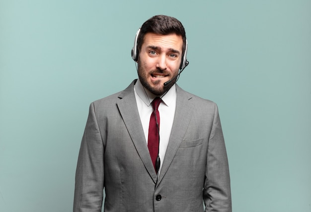 Young businessman looking puzzled and confused, biting lip with a nervous gesture, not knowing the answer to the problem telemarketing concept