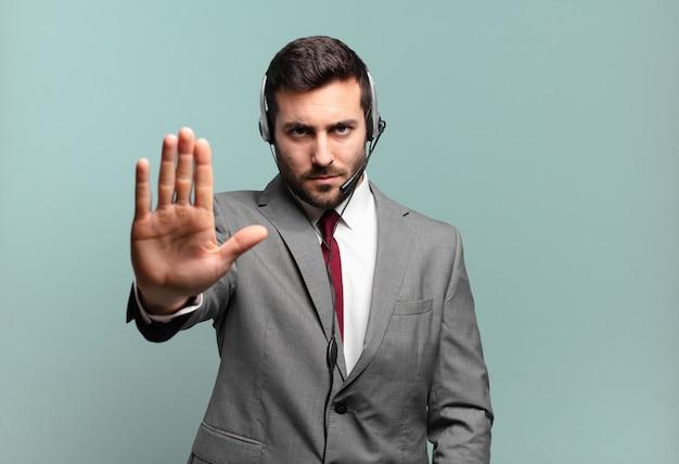 真剣で、厳しく、不機嫌で、怒っているように見える若いビジネスマンは、手のひらを広げて停止ジェスチャーのテレマーケティングのコンセプトを示している