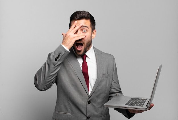 Young businessman looking shocked, scared or terrified, covering face with hand and peeking between fingers and holding a laptop
