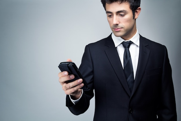 Young businessman looking at smartphone