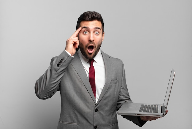 Young businessman looking surprised, open-mouthed, shocked, realizing a new thought, idea or concept and holding a laptop