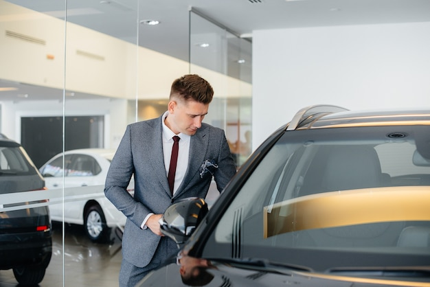 A young businessman looks at a new car in a car dealership. buying a car.